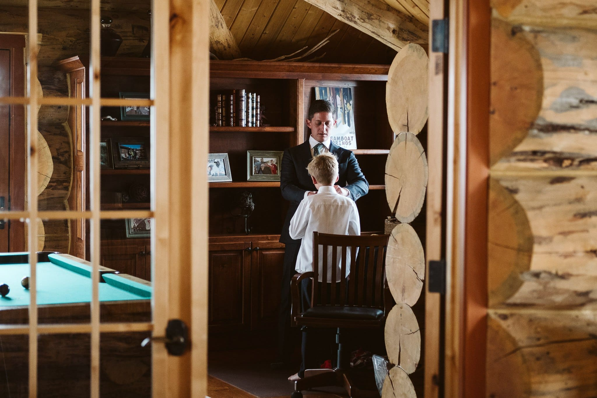 Groom and son getting ready for intimate wedding in mountain home