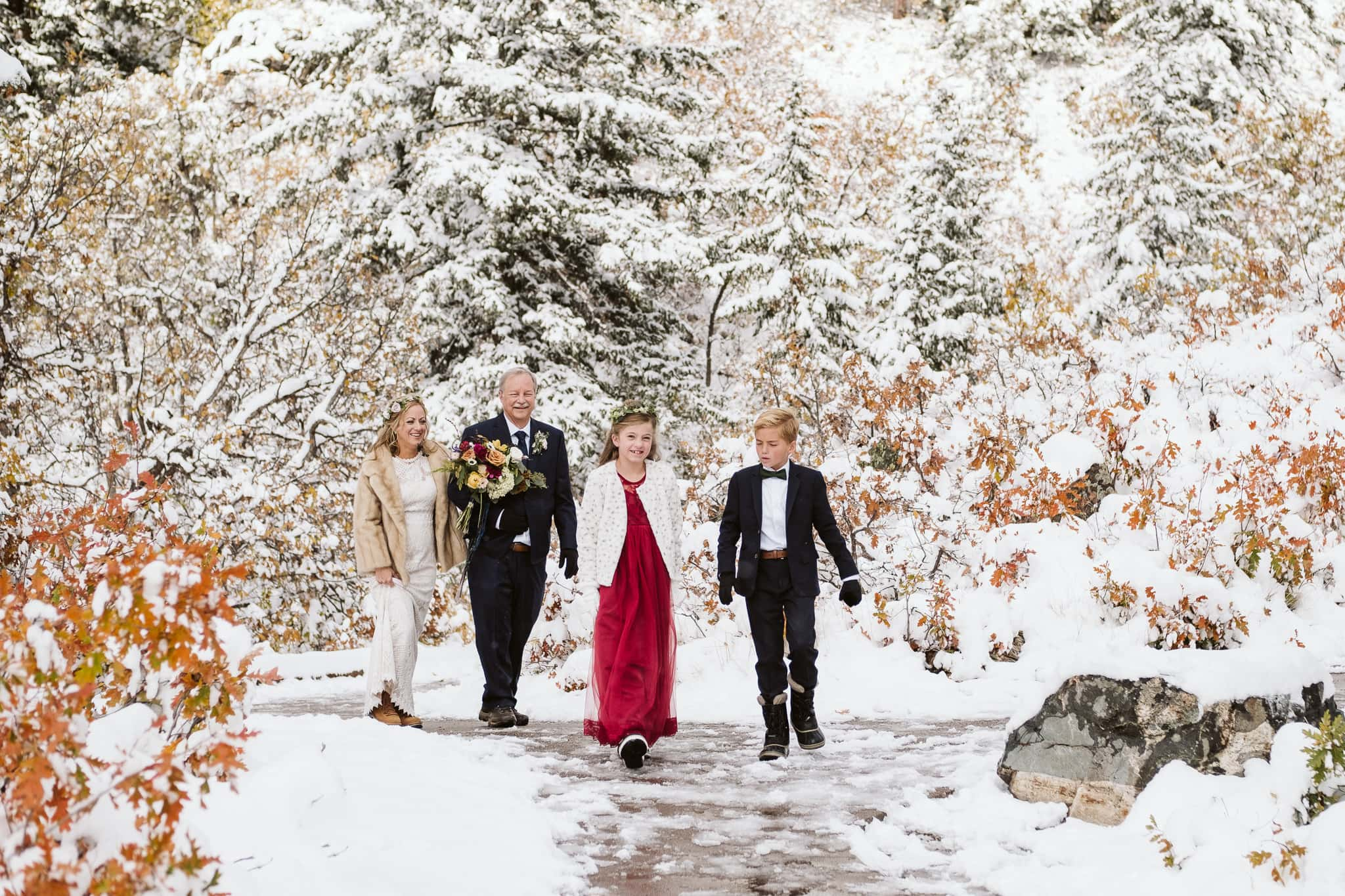 Bride walks down the aisle with her father and children at Fish Creek Falls wedding in Steamboat Springs