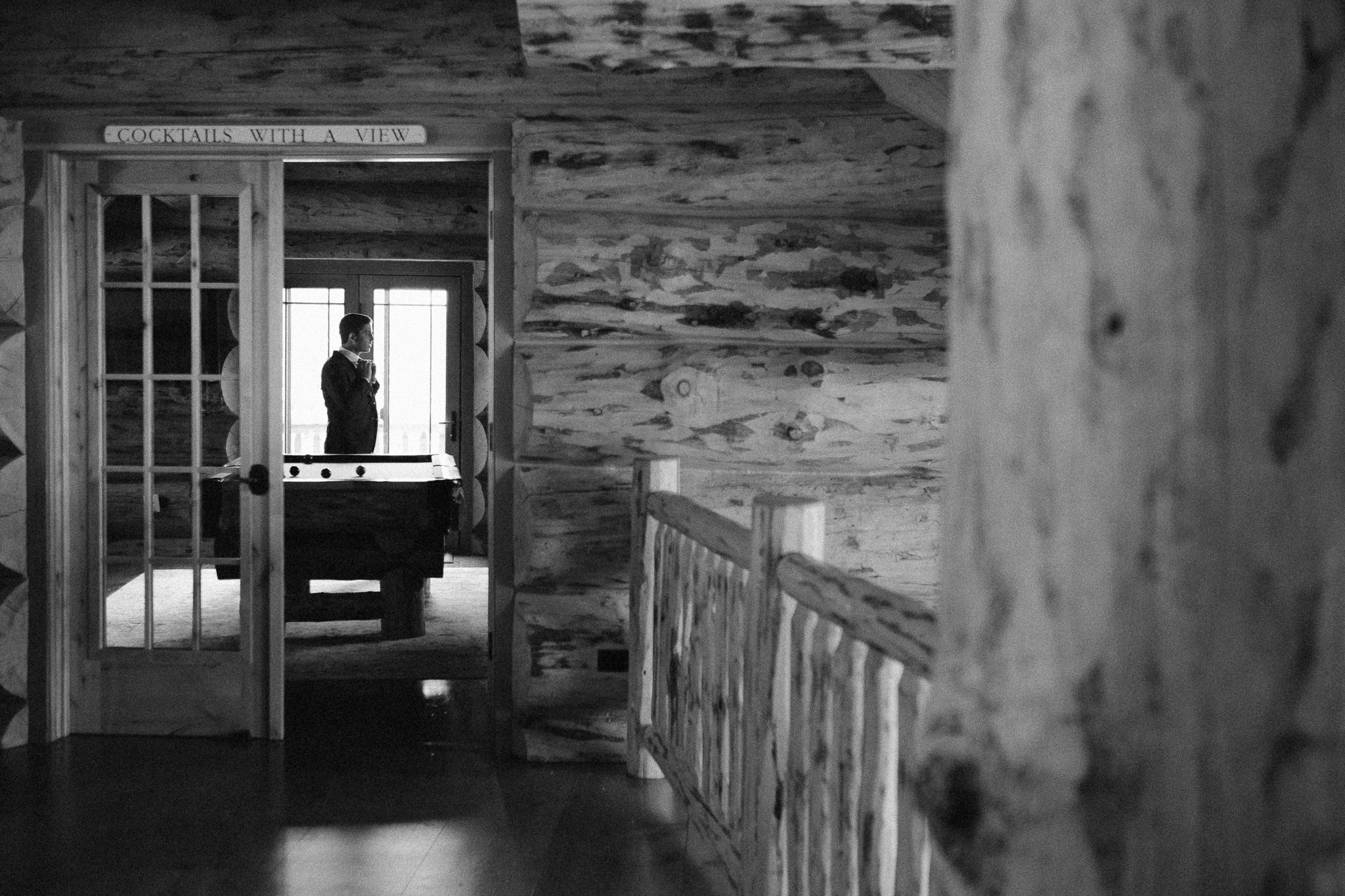 Groom getting ready for elopement in log mountain home in Steamboat Springs. Colorado AirBnB wedding.