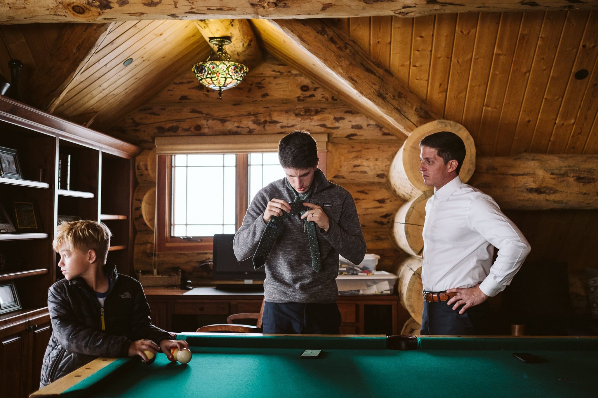 Groom getting ready for elopement in log mountain home in Steamboat Springs