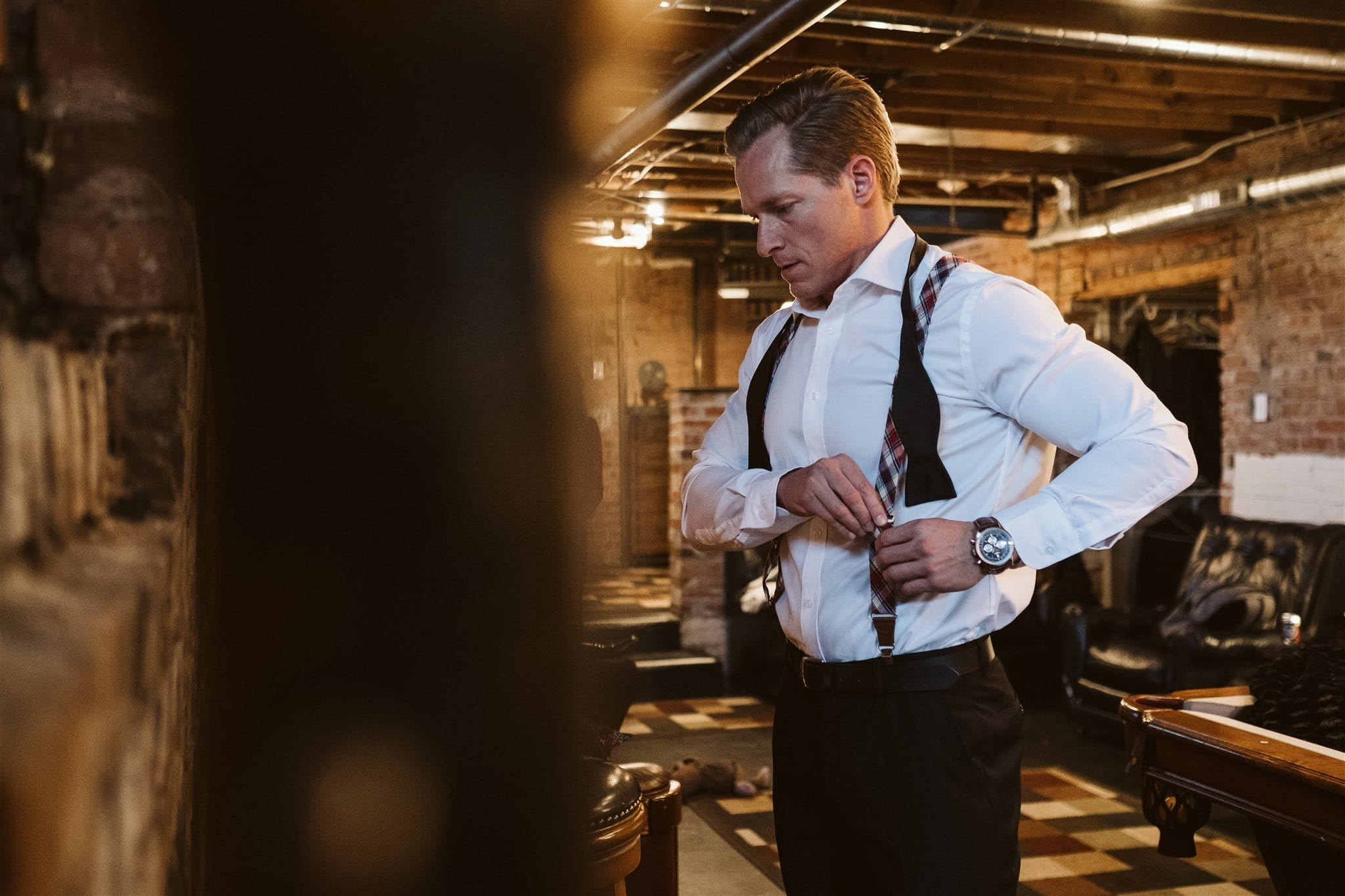 Groom putting on suspenders in the basement at Manor House