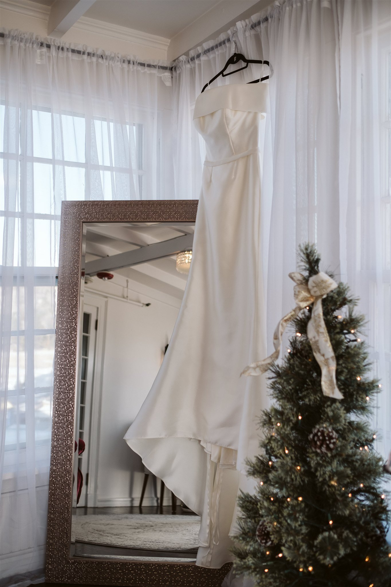 Classic satin wedding dress hanging next to Christmas tree
