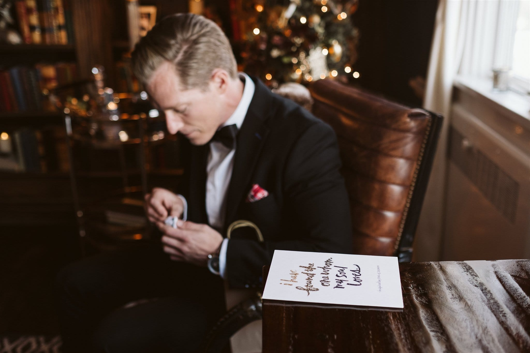 Groom opening card and gift from the bride in the library at the Manor House wedding venue