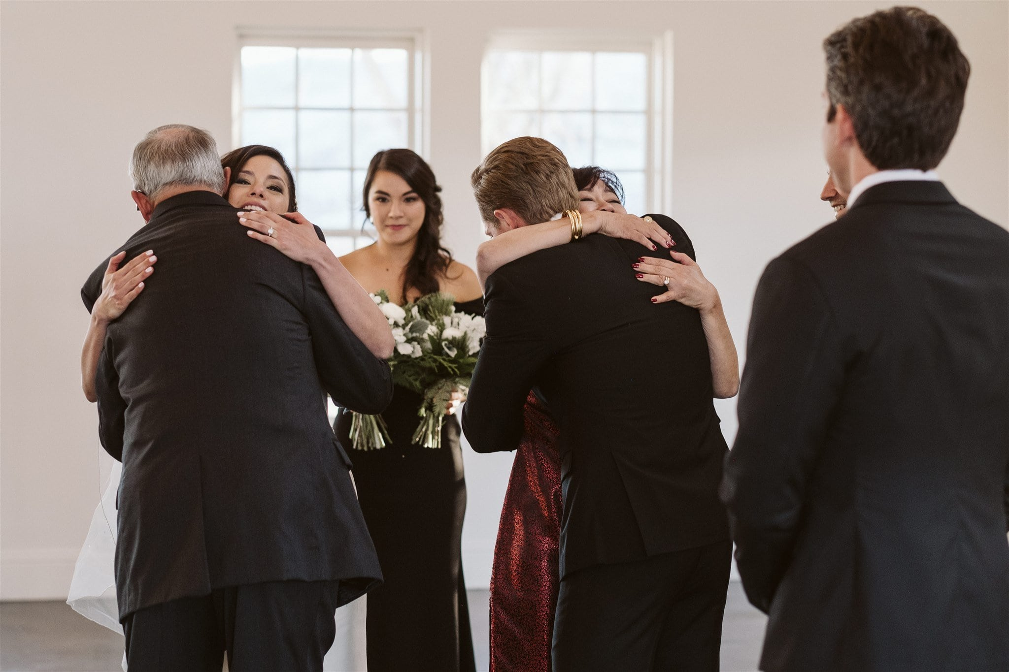 Bride and groom hug their parents