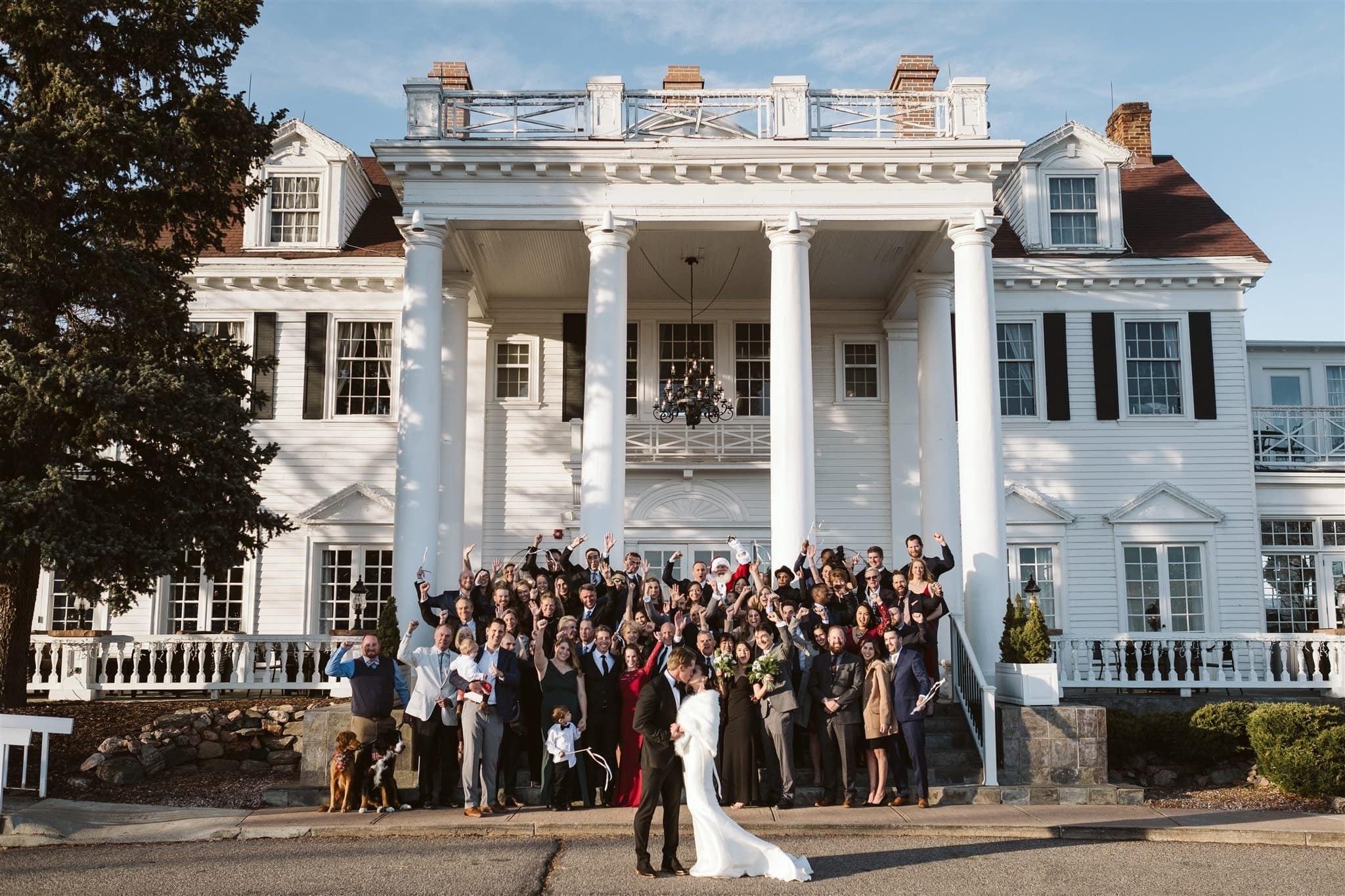 Bride and groom with all their guests outside of The Manor House in Littleton