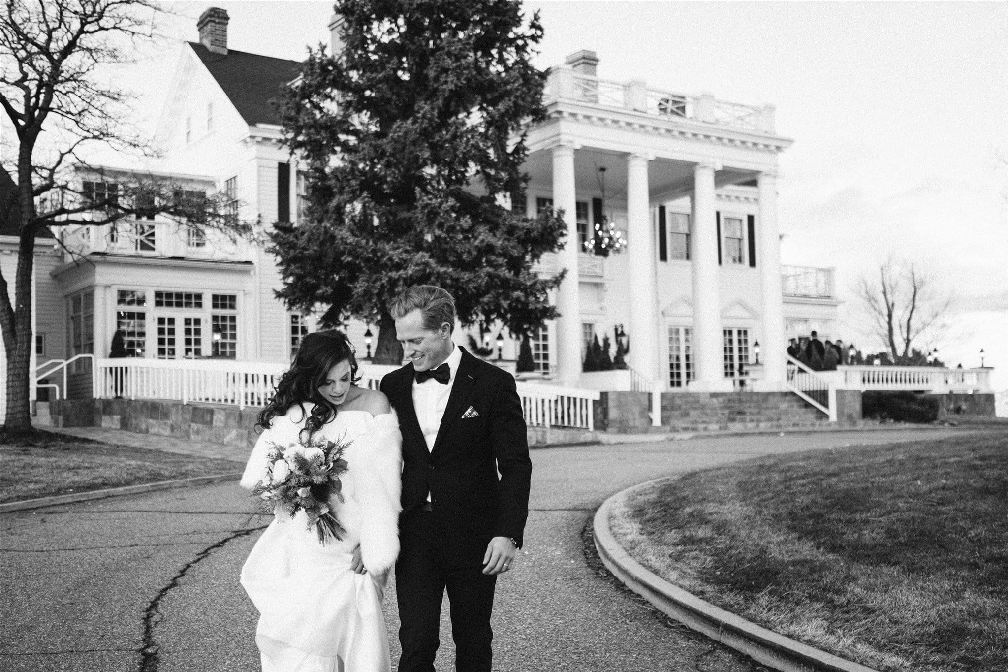 Bride and groom walking in front of the Manor House for wedding portraits