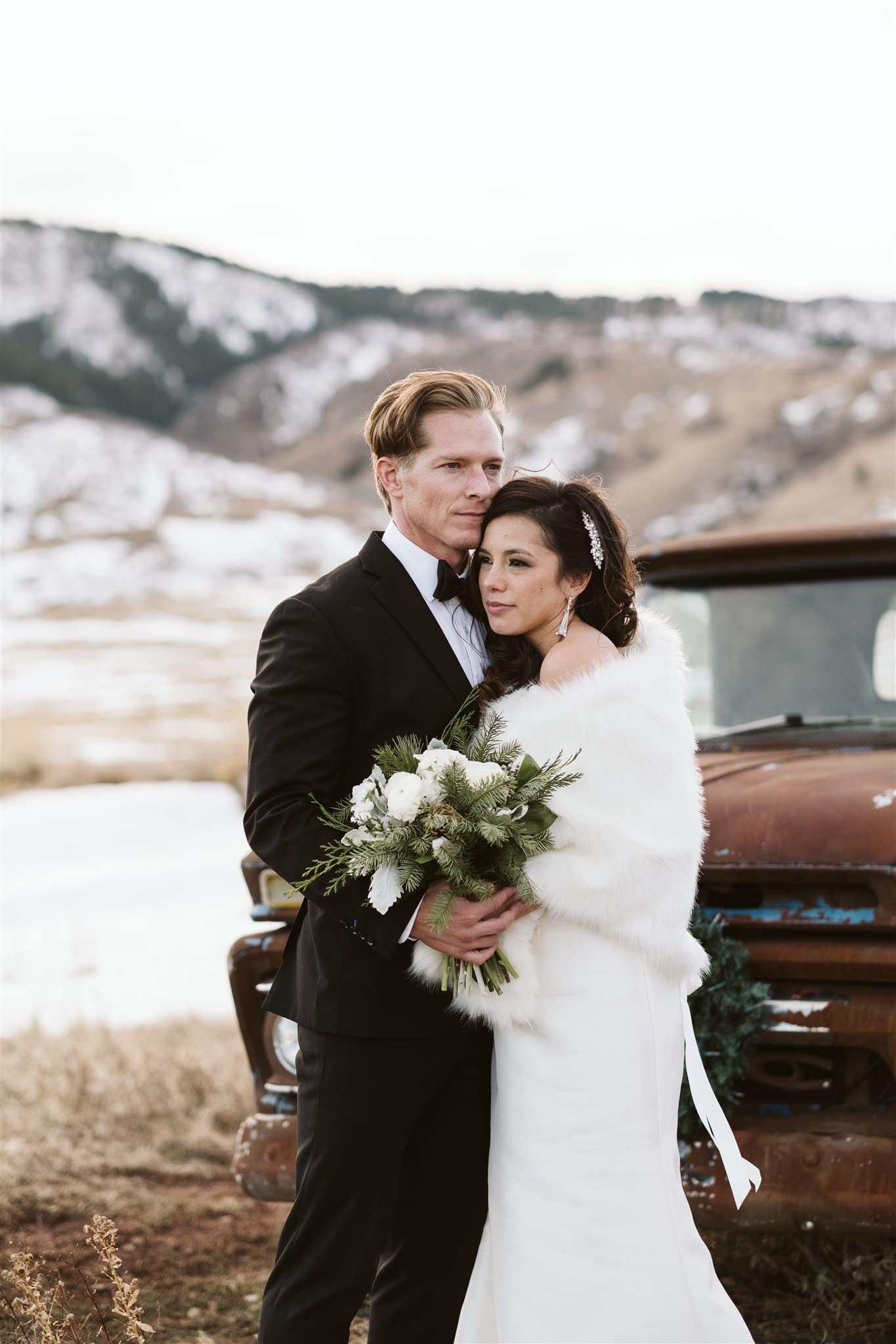 Bride and groom in front of rusty old truck