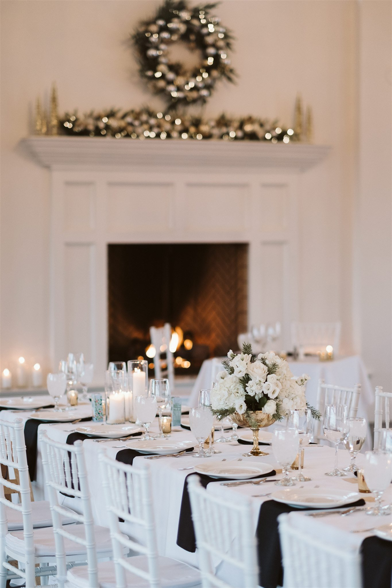 Winter wedding reception decor with white and green flowers and evergreens
