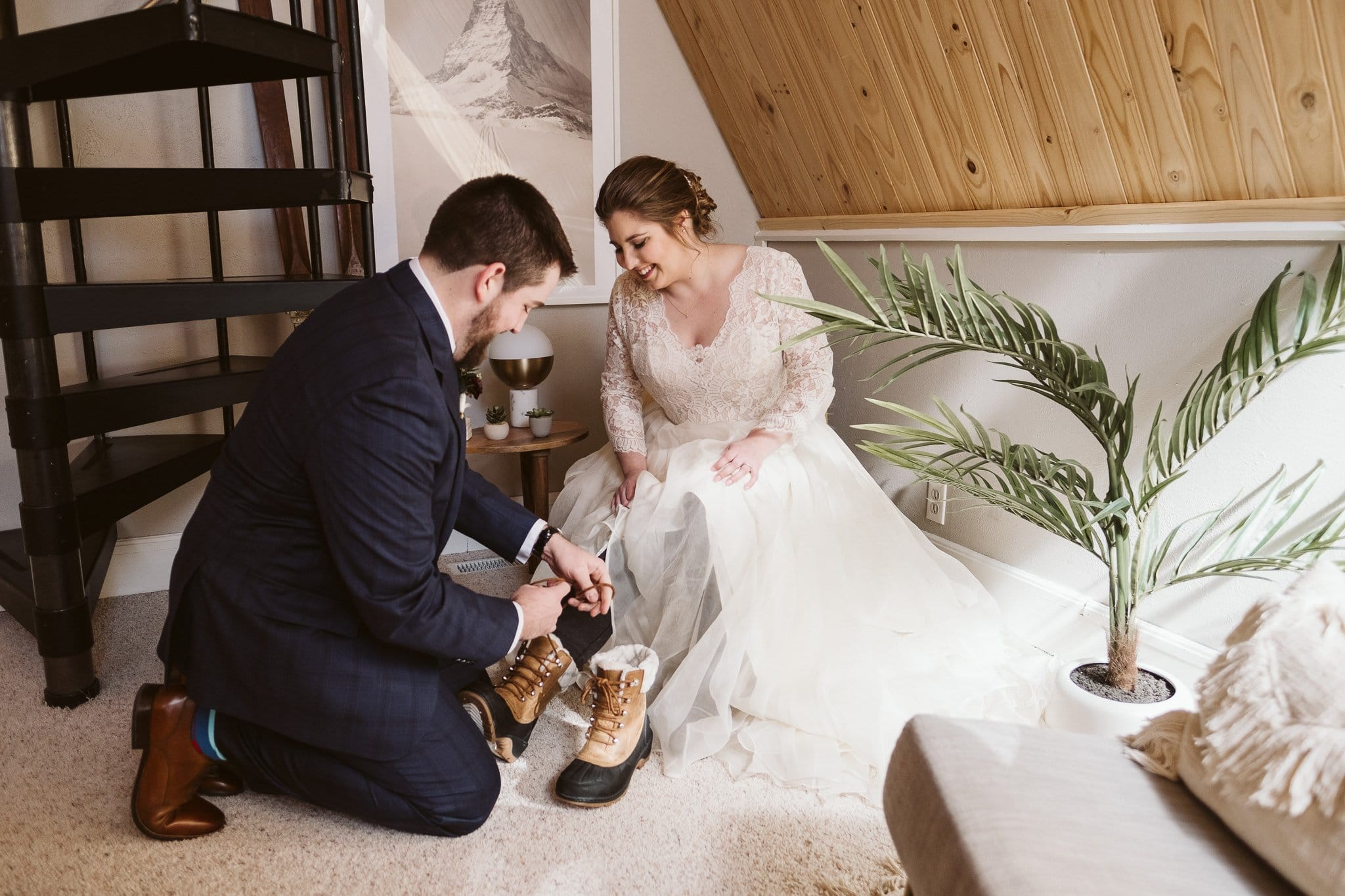 Groom helping bride put on ski boots at winter elopement in Breckenridge, Colorado.