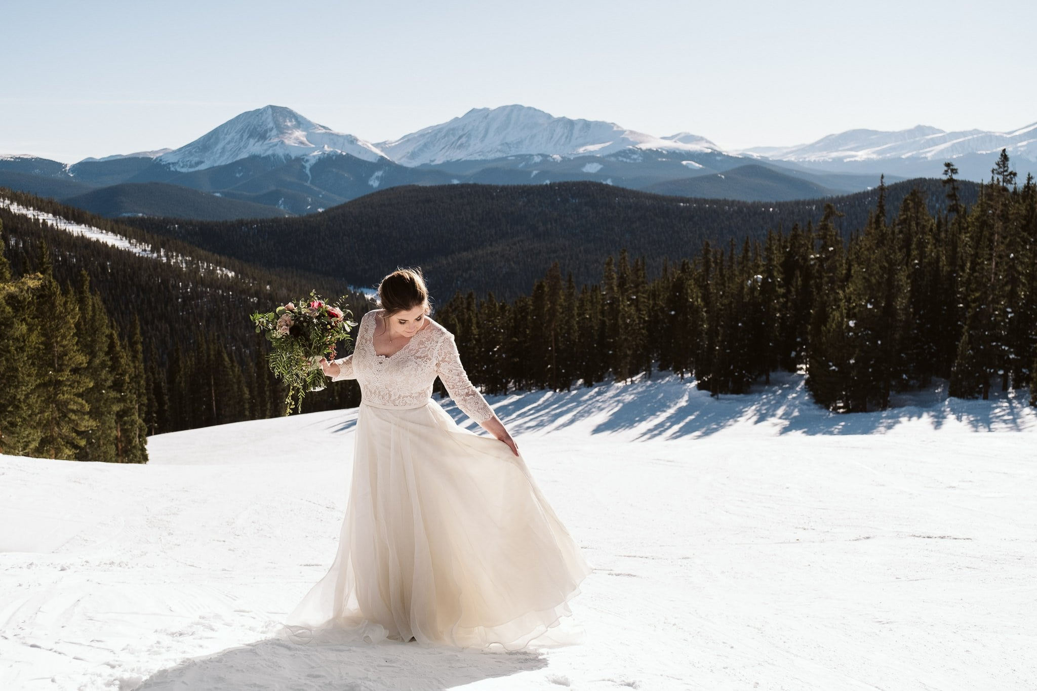 Bride wearing off-white long sleeve wedding dress at winter elopement in the snow.