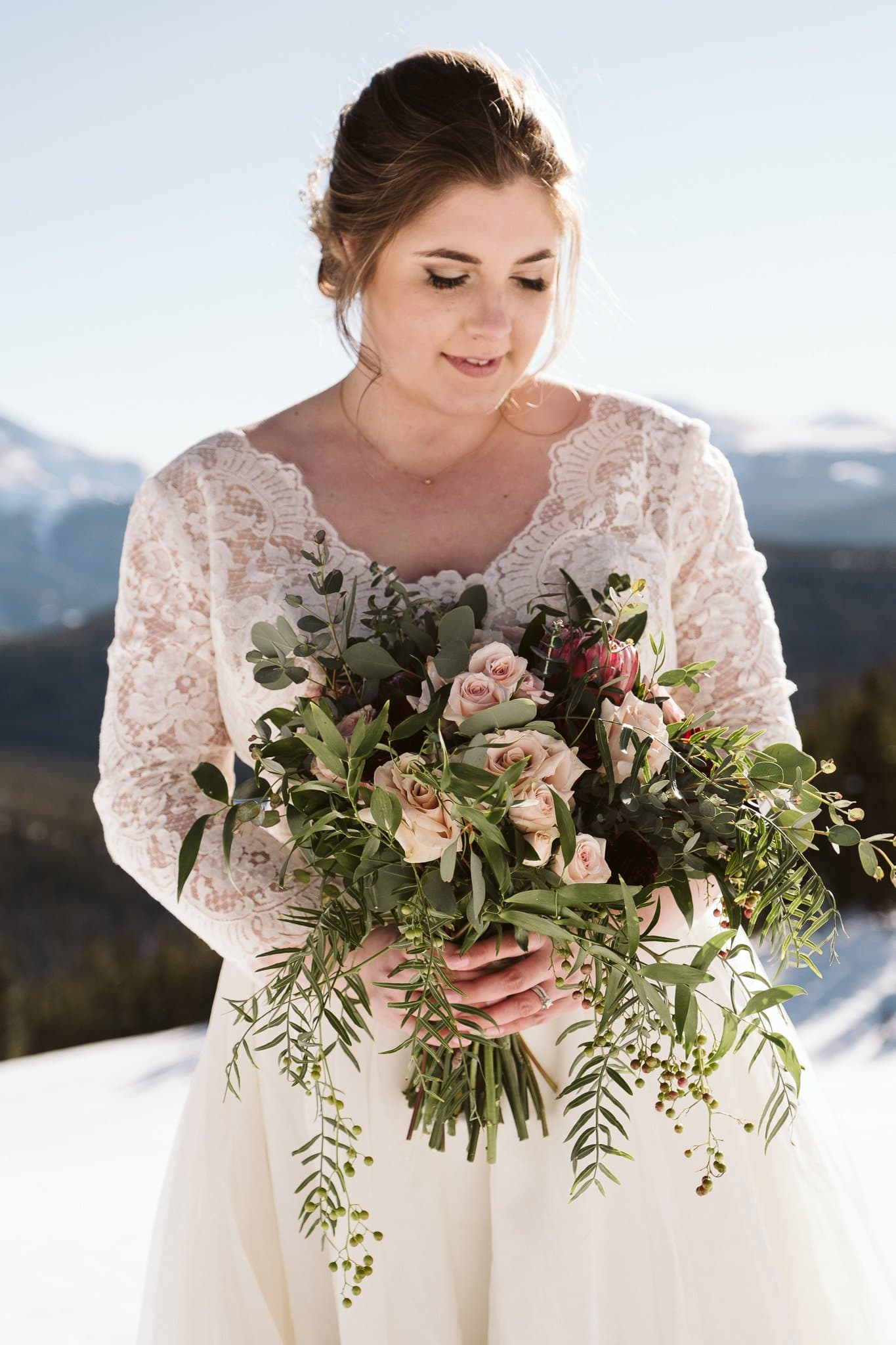 Bride with long sleeve lace wedding dress at winter wedding, holding modern green bouquet with pink and purple flowers.