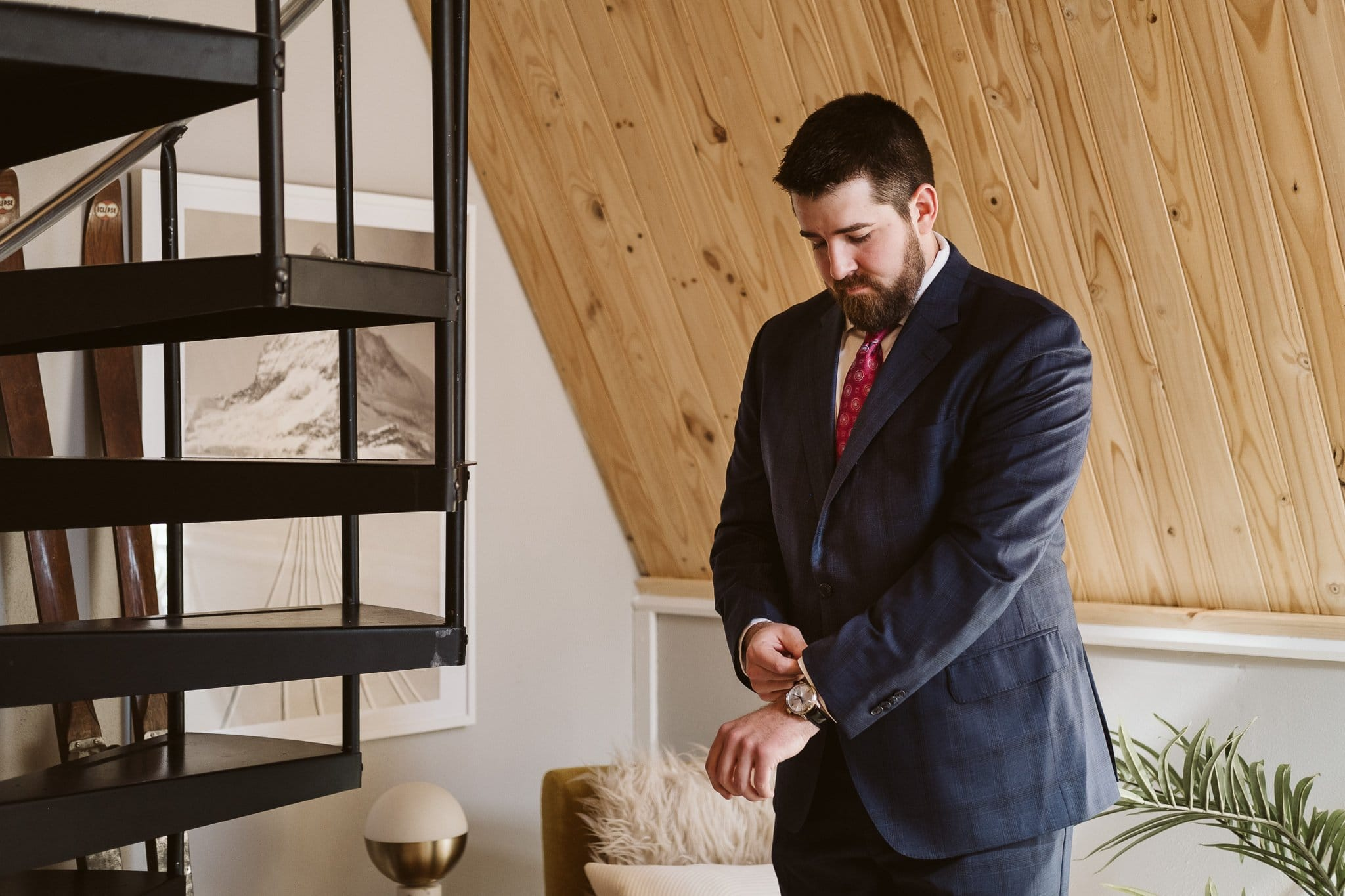 Groom getting ready for elopement in an A-Frame cabin in Breckenridge.