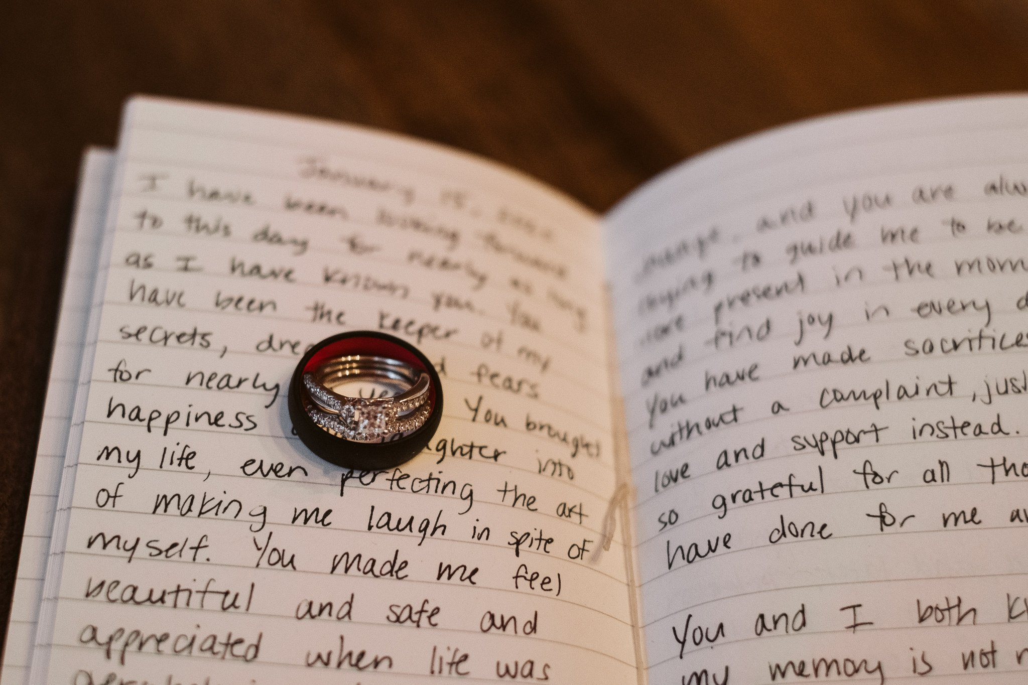 Wedding bands and engagement ring on top of vow book