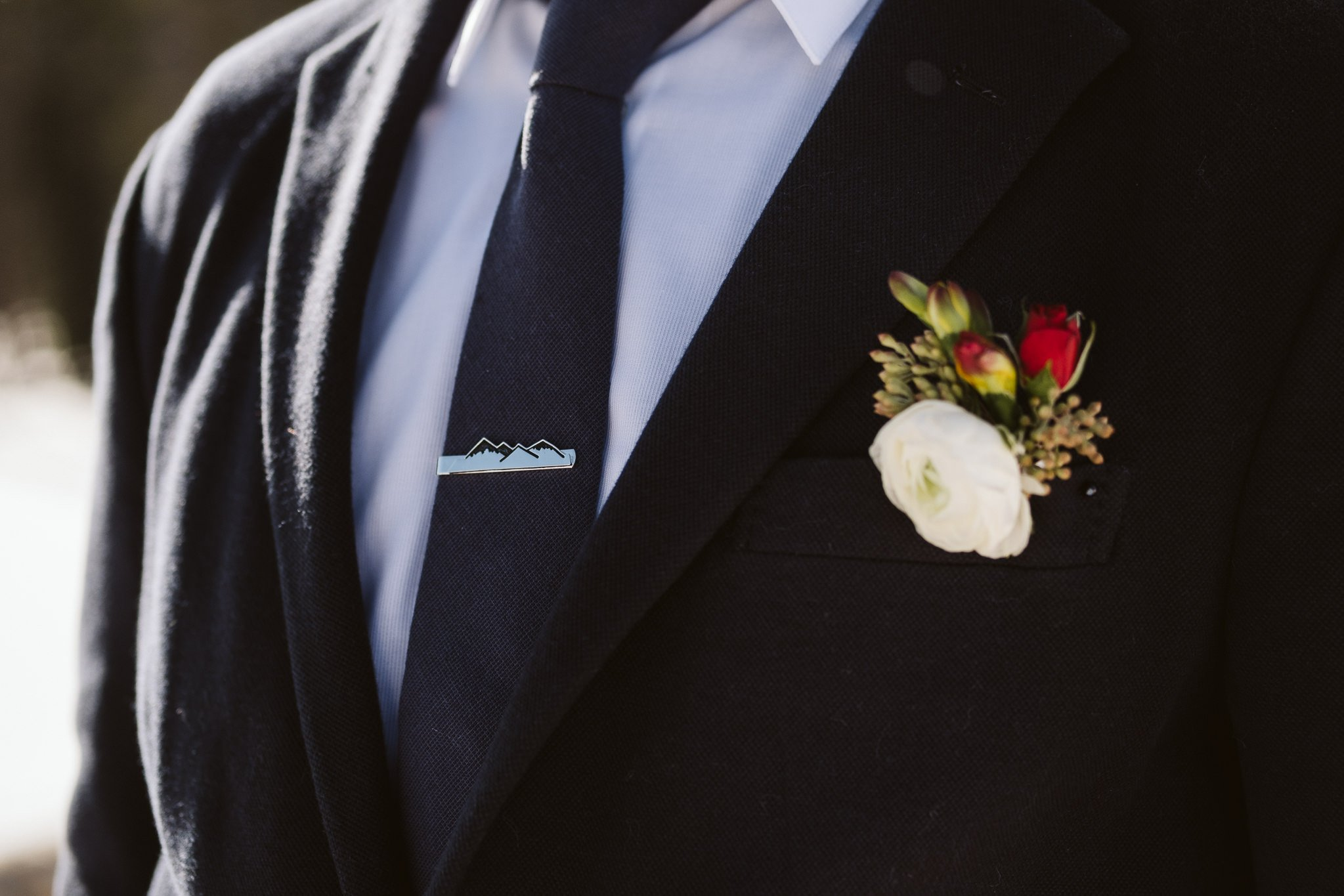 Groom wearing mountain tie clip.