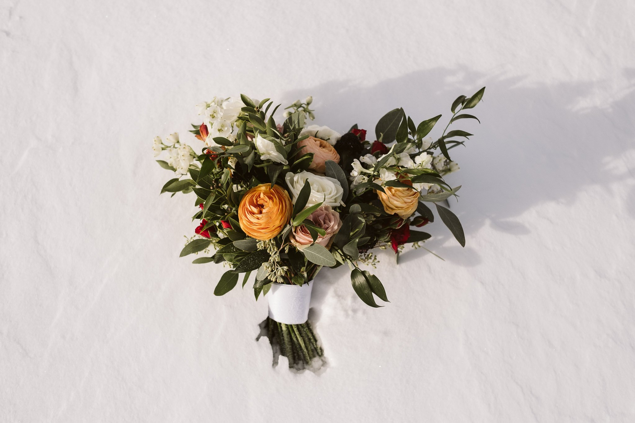 Wedding bouquet with orange and yellow flowers in snow