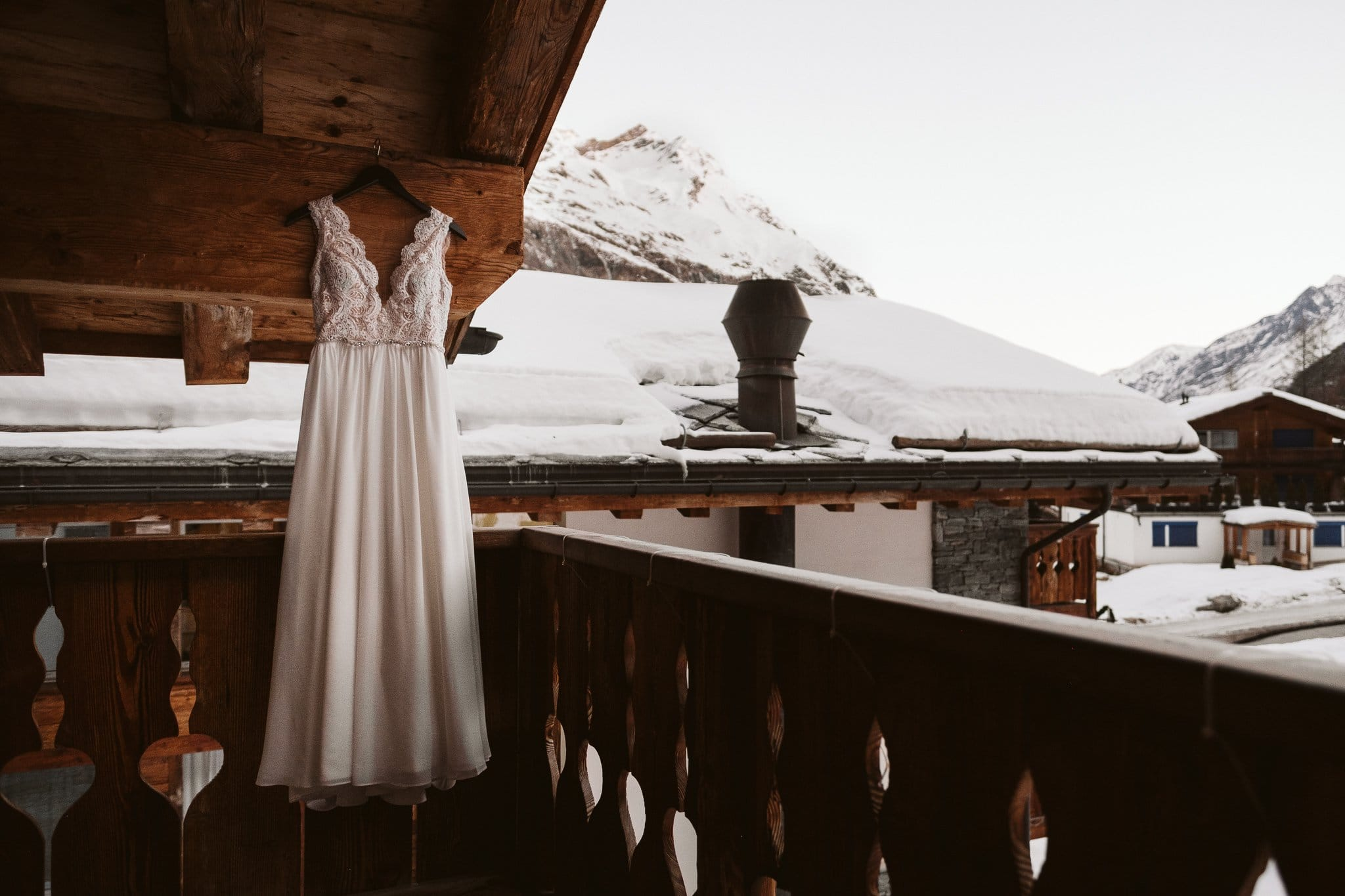 Wedding dress hanging on balcony of traditional Swiss hotel. Matterhorn elopement in Switzerland.