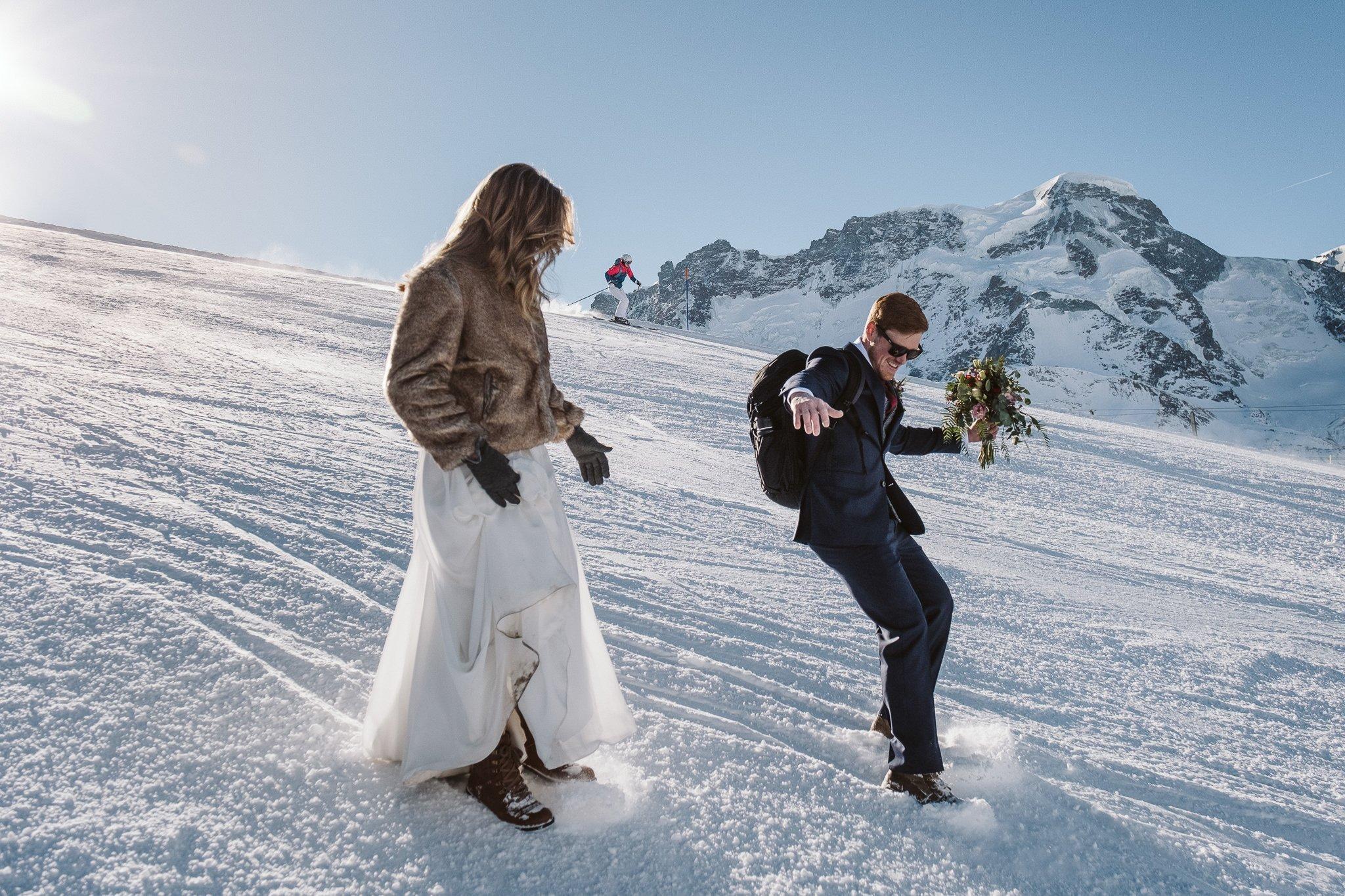 Groom bootskiing on ski slopes of Zermatt Matterhorn in Switzerland elopement.