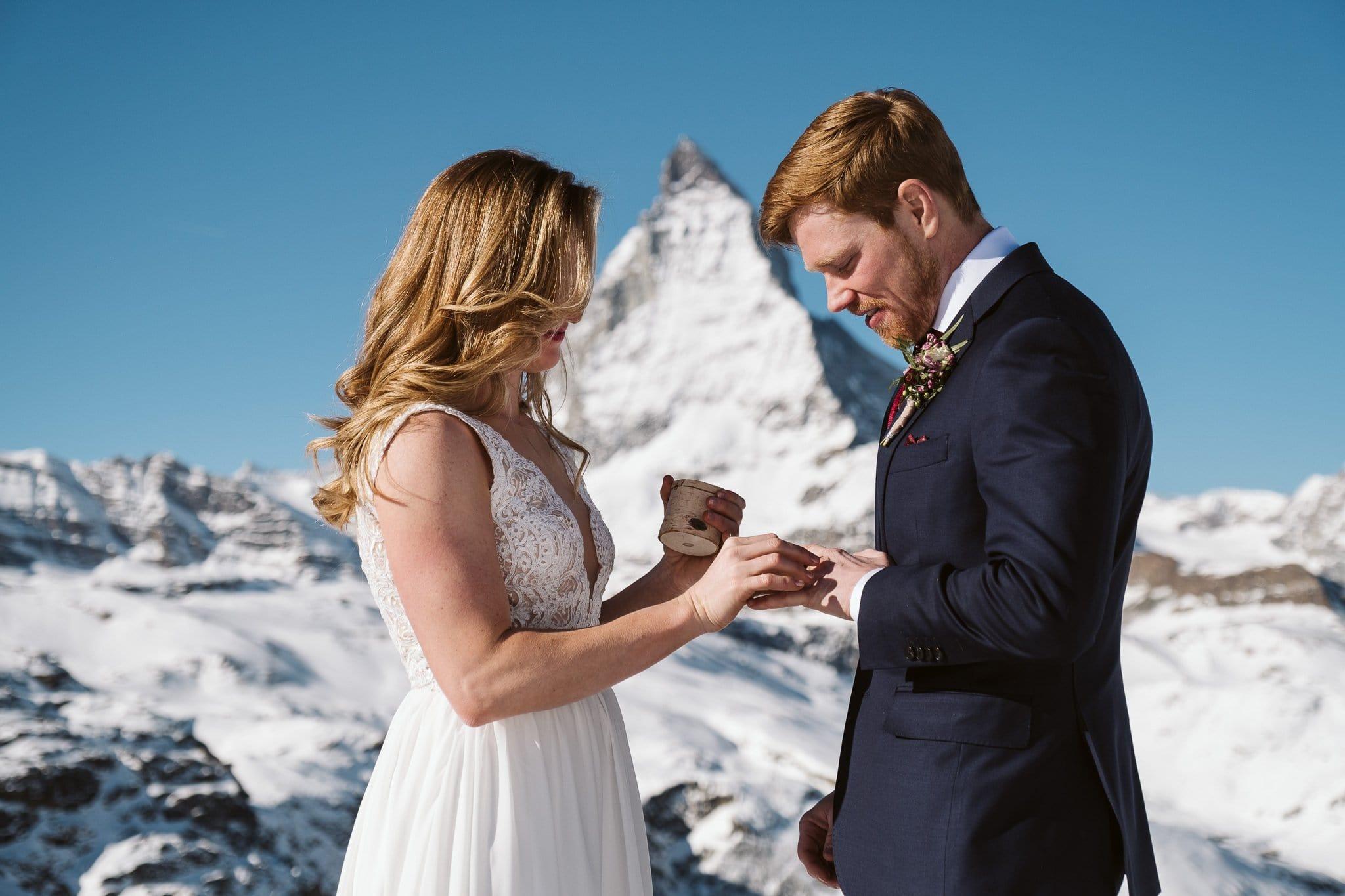 Bride and groom exchange wedding rings in front of Matterhorn in Zermatt. Switzerland elopement photographer.