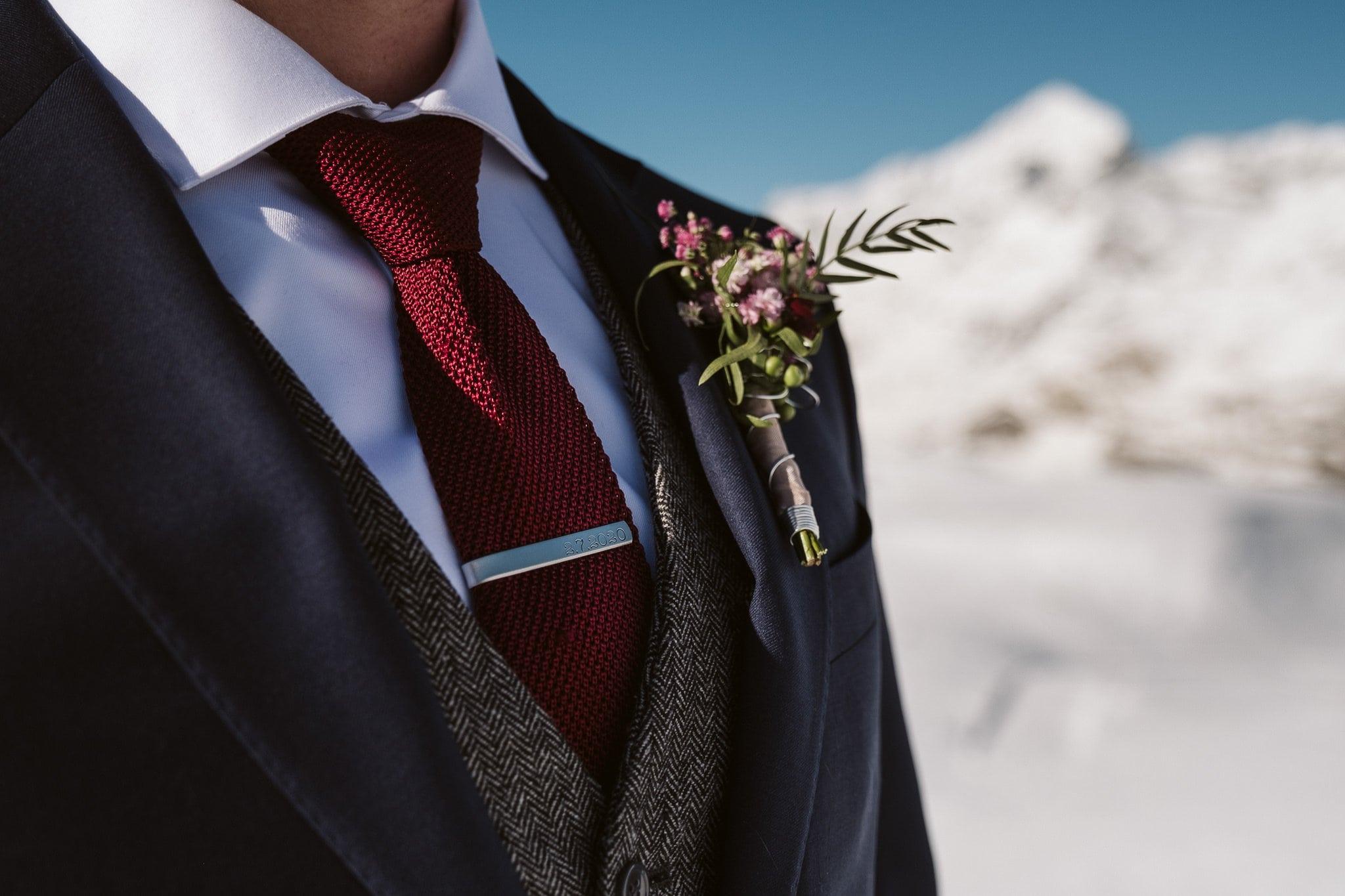 Groom wearing three-piece tweed suit in front of Matterhorn in Zermatt, Switzerland wedding photographer. Tie clip with wedding date engraved.