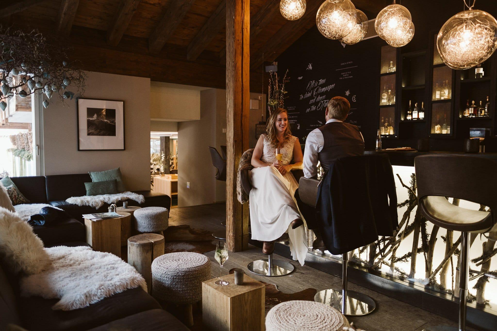 Bride and groom having cocktails at Matthiol Boutique Hotel in Zermatt, Switzerland.