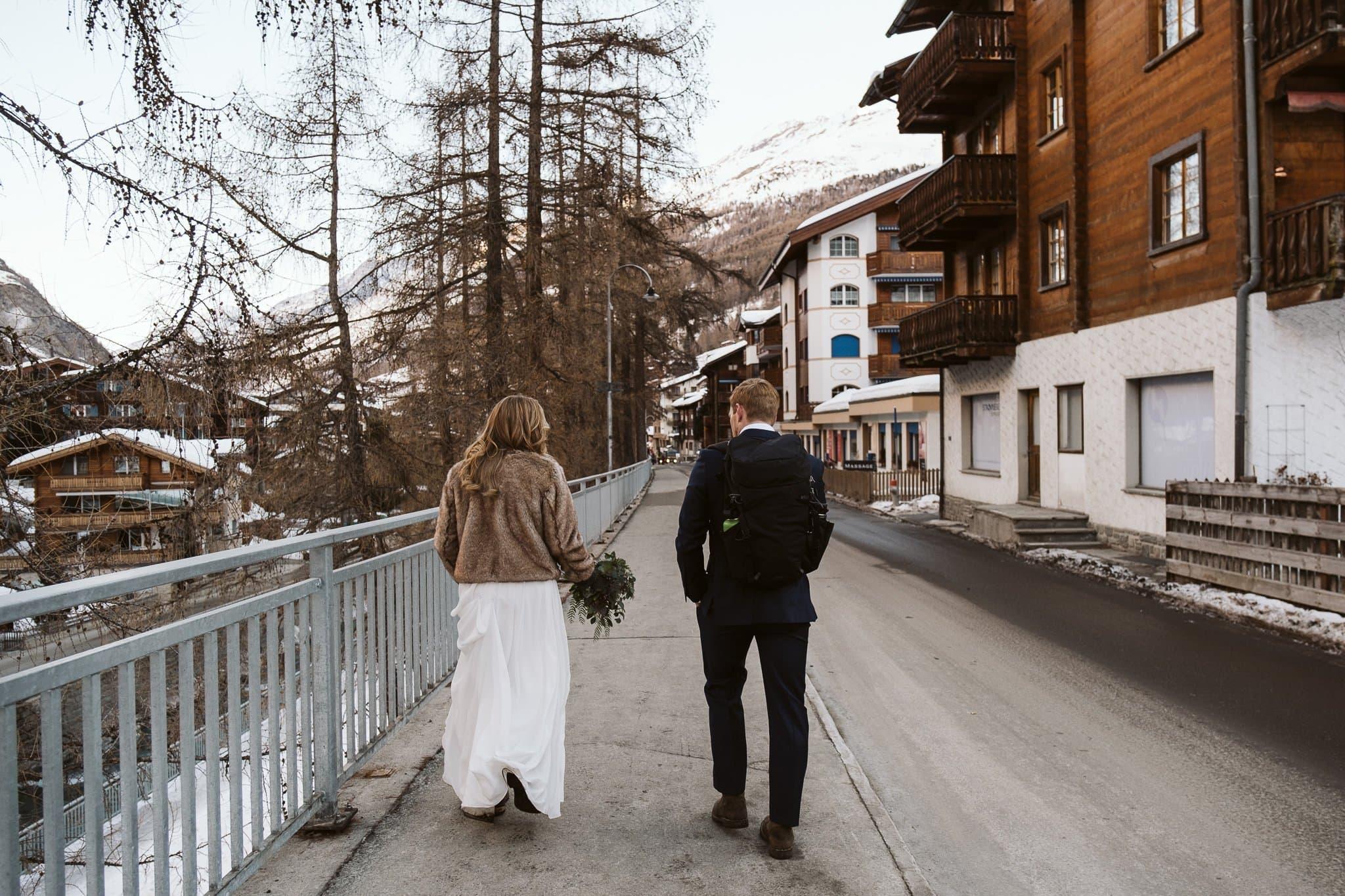 Bride and groom walking through streets of Zermatt