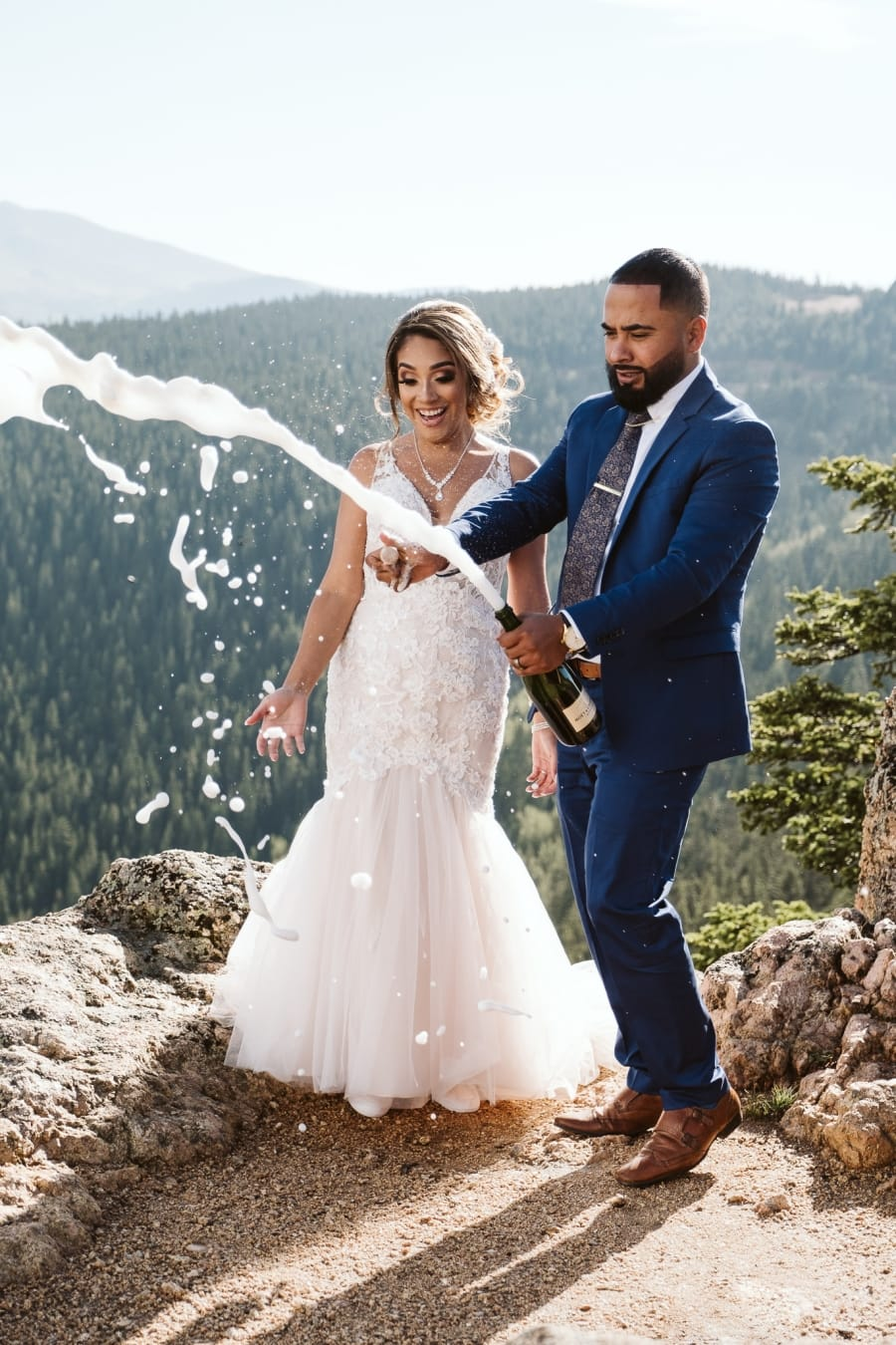 Bride and groom popping champagne at Colorado elopement