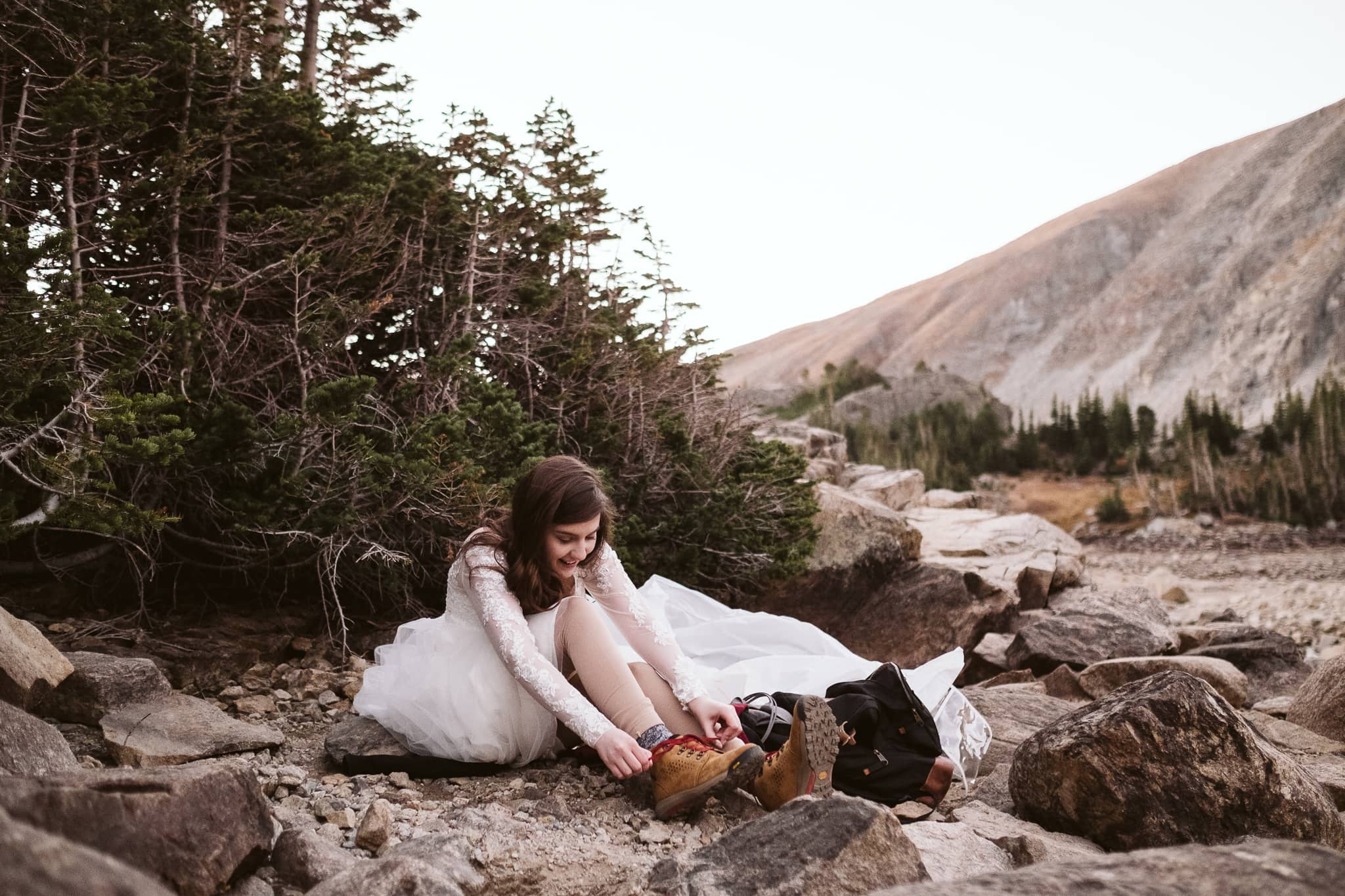 Bride putting on hiking boots for elopement