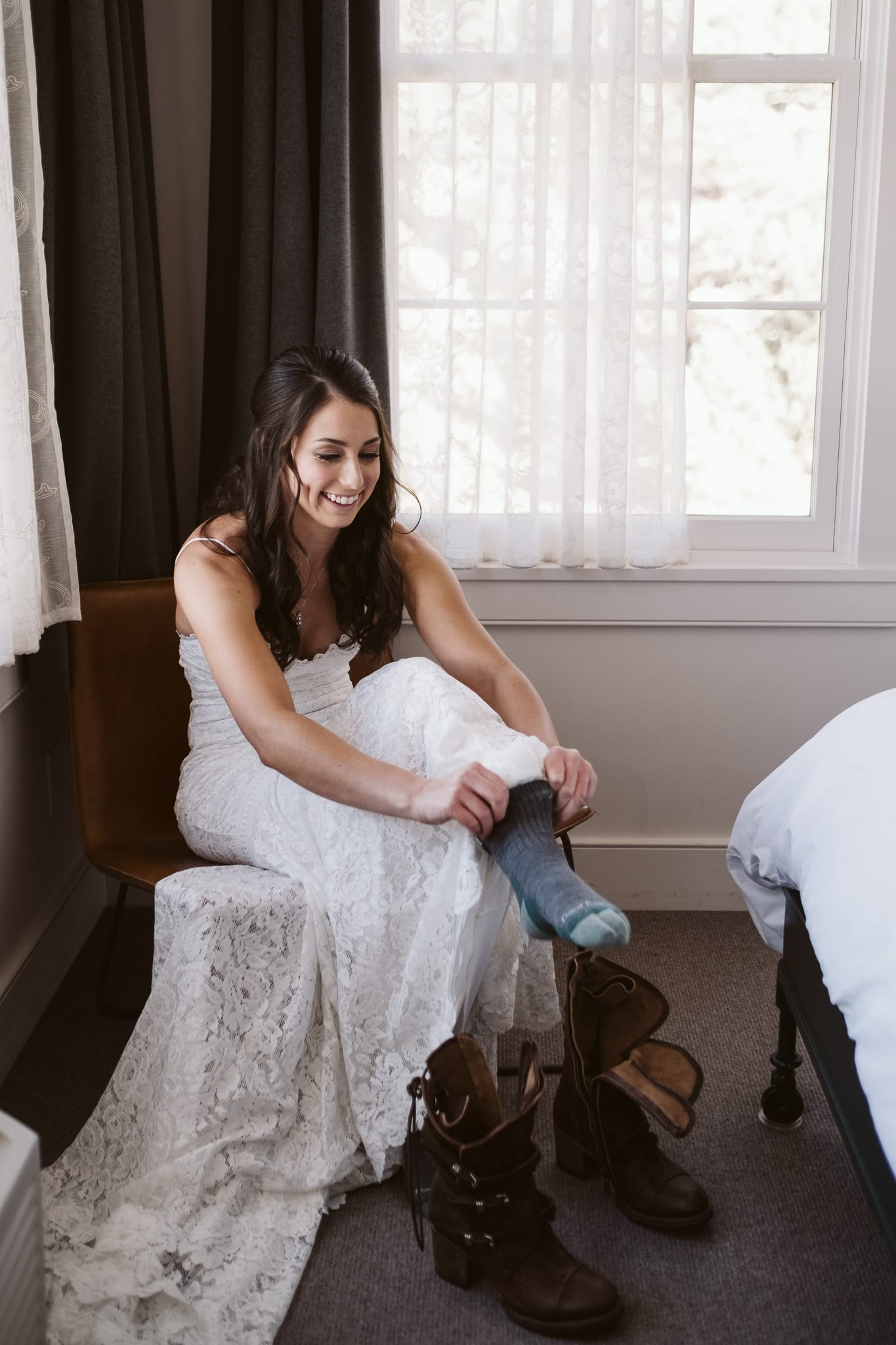 Bride putting on Darn Tough socks for her elopement